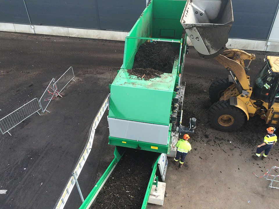 TAKER T-18 with discharge conveyor and top loader barrier in a plant of biomass and green waste conditioning